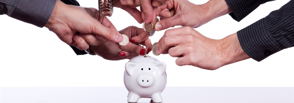 many hands putting money into a piggy bank